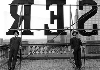 Collin and David Leaning on Rooftop Letters, Alberta, Canada, 2004